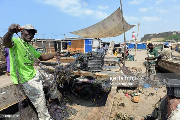 A fishermqn tries to mend a fishing net on the beach in the Jamestown district central Accra on July 14 2017 Jamestown one of poorest fishing...