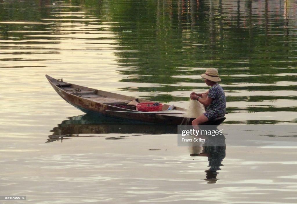 Fisherwoman fishing at dawn on the Thu Bon river, Hoi An, Vietnam : Stockfoto