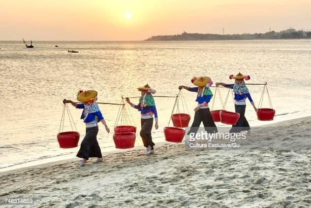 fisherwomen in traditional clothes carrying shoulder yokes on beach, dazuo, fujian, china - yoke stock photos and pictures