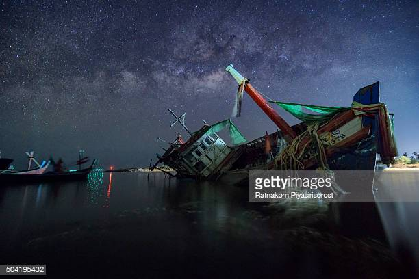 fishery ship wrecked in thailand with milky way at night time. - sunken stock pictures, royalty-free photos & images