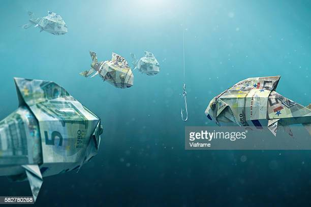 Fishes built of money swimming to fishhook