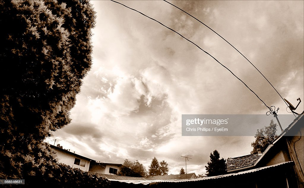Fish-Eye Lens Of Houses By Trees Against Cloudy Sky : Stock Photo
