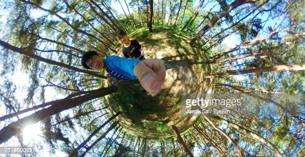 Fish-Eye Lens Of Man And Girl Standing In Forest