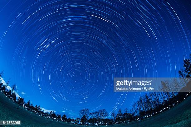 Fish-Eye Lens Of Road Against Sky With Star Trails