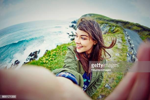 fish-eye lens of woman taking selfie on mountain by sea - fish eye foto e immagini stock