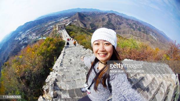 fish-eye lens portrait of smiling woman against mountain range - grande angular - fotografias e filmes do acervo