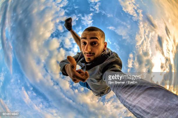 fish-eye lens portrait of young man showing thumbs up amidst clouds - fish eye lens stock pictures, royalty-free photos & images