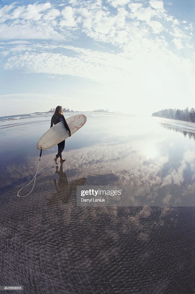 Fisheye Lens Shot of a Man Carrying a Surfboard on an Isolated Beach : Stock Photo