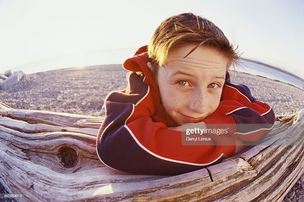 Fisheye Lens Shot of a Young Boy Leaning Against a Log on a Pebbled Beach : Stock Photo