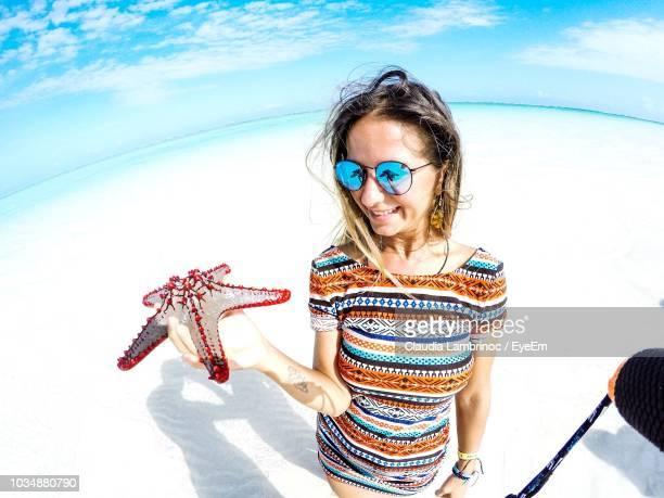 fish-eye lens shot of smiling young woman holding starfish at beach during summer - east africa stock pictures, royalty-free photos & images