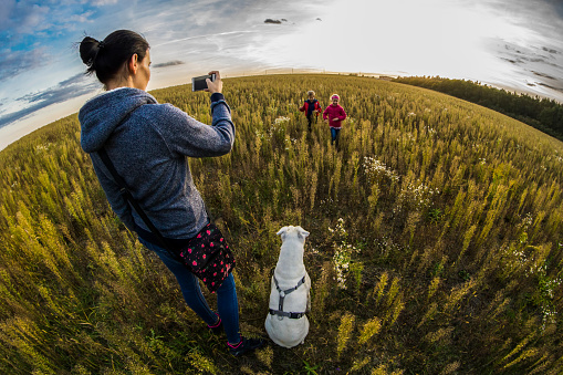 Fish-Eye Lens View Of Mother Photographing Children Running On Field - gettyimageskorea