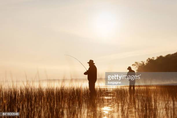 angeln bei sonnenaufgang - fischer stock-fotos und bilder