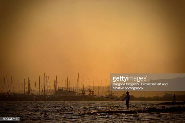 fishing at sunset - gregoria gregoriou crowe fine art and creative photography. stockfoto's en -beelden