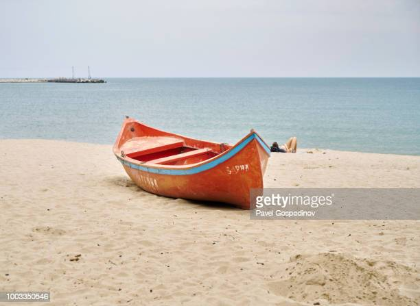 A fishing boat and a tourist sunbating on a the city beach in Varna, Bulgaria (cinematic look)