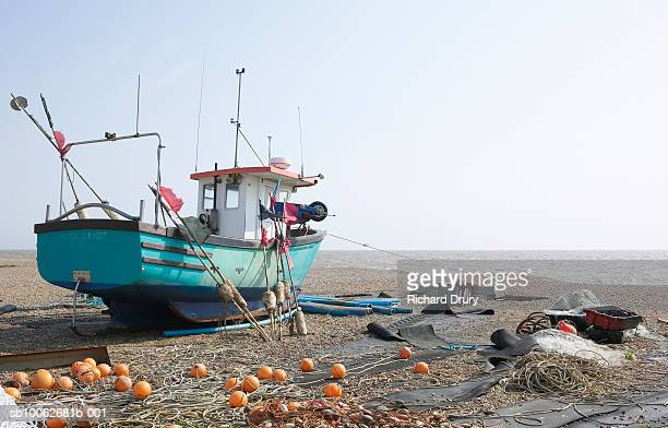 fishing boat and equipment on beach - richard drury stock pictures, royalty-free photos & images