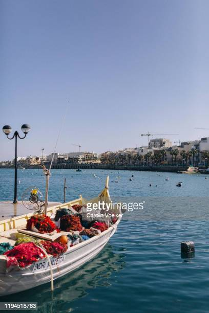 fishing boat full of rolled up fishing nets in the harbour bay of  marsaskala, malta - marsaxlokk stock pictures, royalty-free photos & images