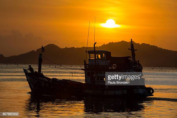 A fishing boat heads off to sea at sunset from the port in Songkhla on February 1 2016 Around 100 people have been arrested by authorities in a...