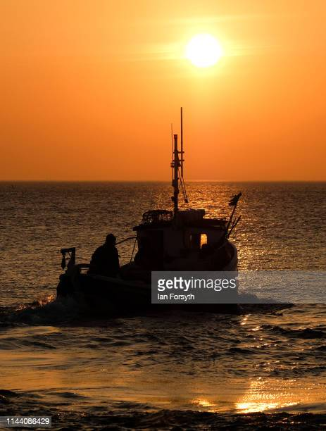 A fishing boat heads out from Whitby Harbour to check lobster and crab pots as the sun rises on Easter Sunday on April 21 2019 in Whitby United...