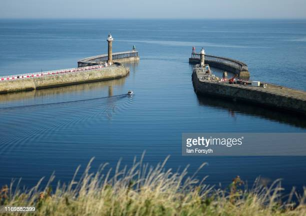 A fishing boat heads out to calm seas from Whitby harbour on August 24 2019 in Whitby England Temperatures are expected to climb over 30C in parts of...