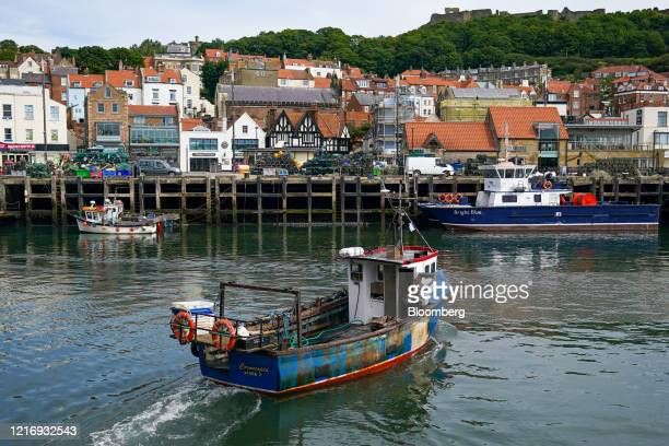 A fishing boat heads to tie up after unloading its catch in the harbour in Scarborough UK on Tuesday June 2 2020 The threat of a nodeal Brexit is...