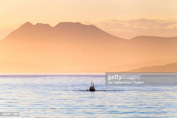 Fishing Boat In Sea With Mountain In Background
