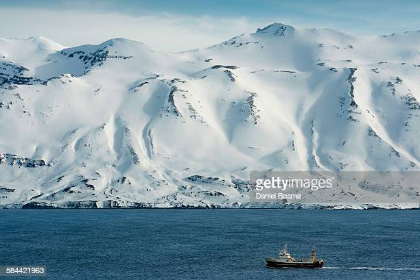 Fishing boat in sea with snow capped mountains