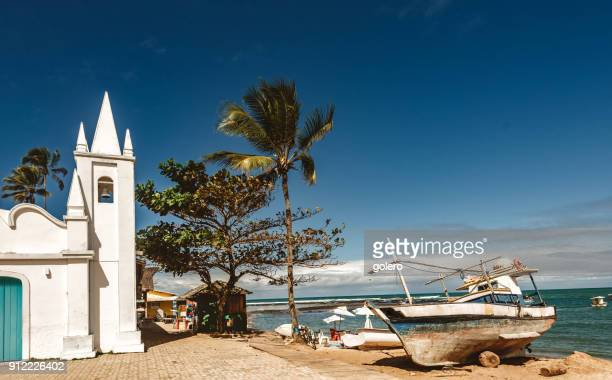 fishing boat in the sand of praia do forte beach in the sun - brasil stock pictures, royalty-free photos & images