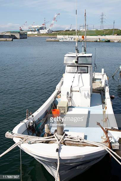 A fishing boat is moored near the reactor building for Electric Power Development Co's Oma nuclear power plant which stands under construction in Oma...