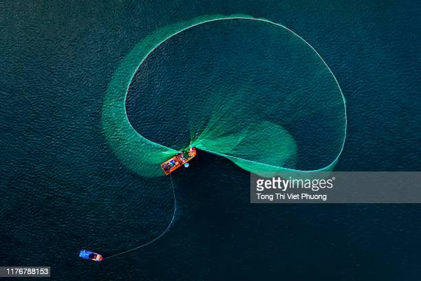 a fishing boat is opening a fish net to catch fishes on the sea of phu yen vietnam - fisherman stock pictures, royalty-free photos & images