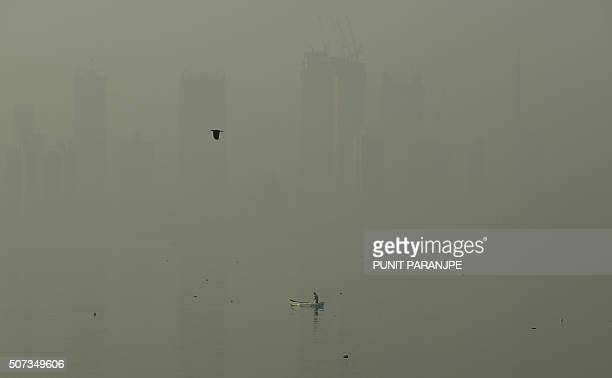A fishing boat is seen in the morning general view of the city skyline covered by a smoggy haze in Mumbai on January 29 2016 AFP PHOTO / PUNIT...