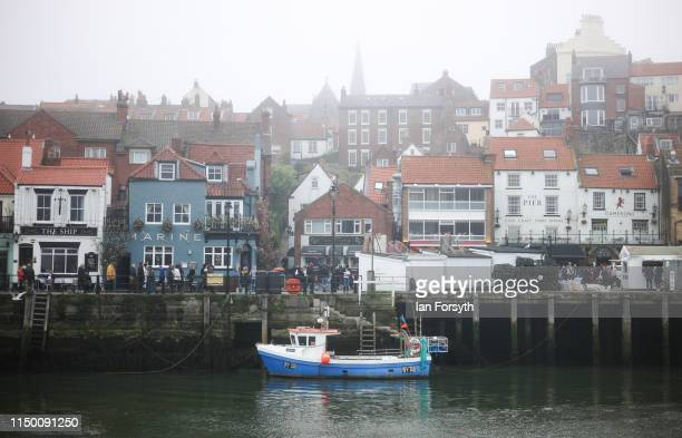 A fishing boat is tied alongside the harbour wall as sea fog shrouds Whitby on May 18 2019 in Whitby England Heavy fog and mist covered many parts of...