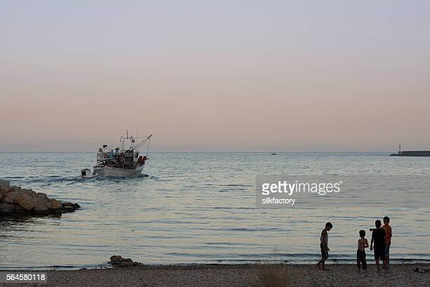 Fishing boat leaves Greek Island harbor at sundown