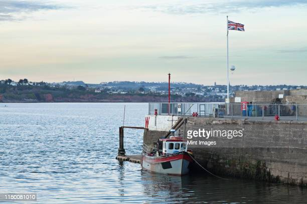 a fishing boat moored by a harbour wall on the english coast. - fishing boat stock pictures, royalty-free photos & images