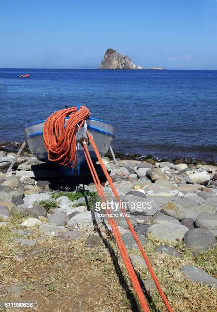 Fishing boat moored on brillant red rope, Panarea beach