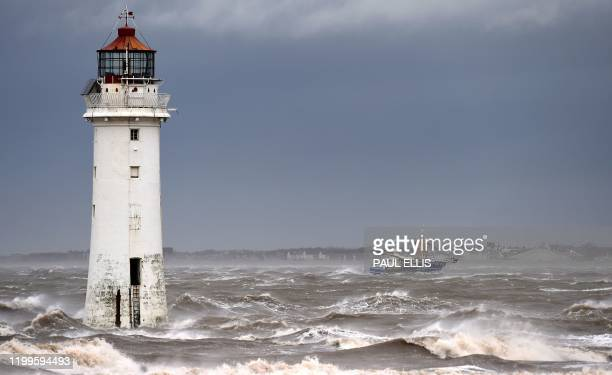 A fishing boat navigates stormy seas as it passes beyond the lighthouse in New Brighton north west England on February 9 as Storm Ciara swept over...
