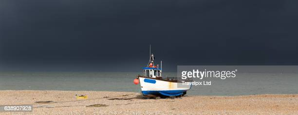 Fishing boat on Beach against stormy sky