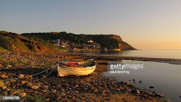 Fishing boat on beach at Runswick Bay as sunrises