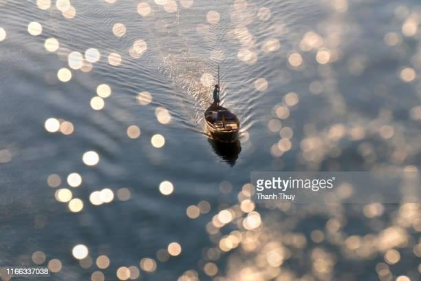 fishing boat on river of bokeh - bateau à rames photos et images de collection