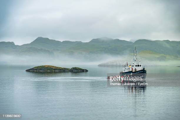 fishing boat on sea against sky - fishing boat stock pictures, royalty-free photos & images