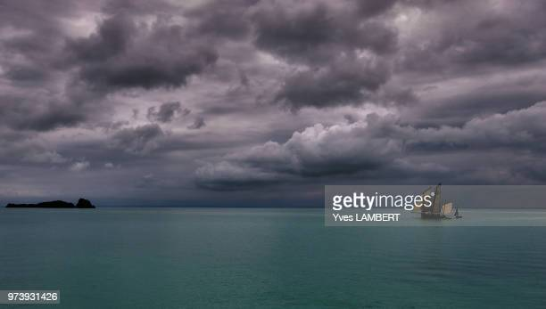 fishing boat on sea and stormy clouds in background, mont st michel, dinard, france - dinard stock pictures, royalty-free photos & images