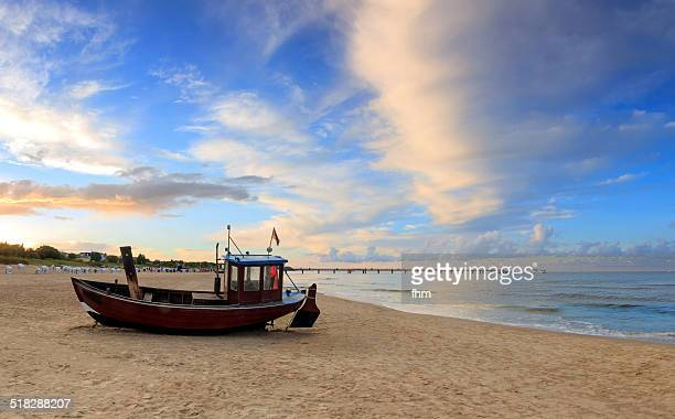 Fishing boat on the beach with cloudy blue sky