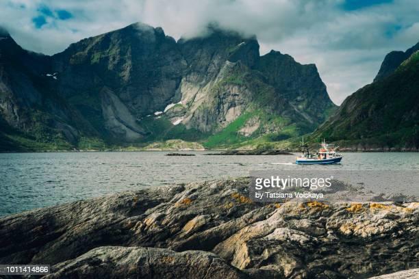 fishing boat on the sea near reine, moskenes, lofoten islands, norway - lofoten stock pictures, royalty-free photos & images