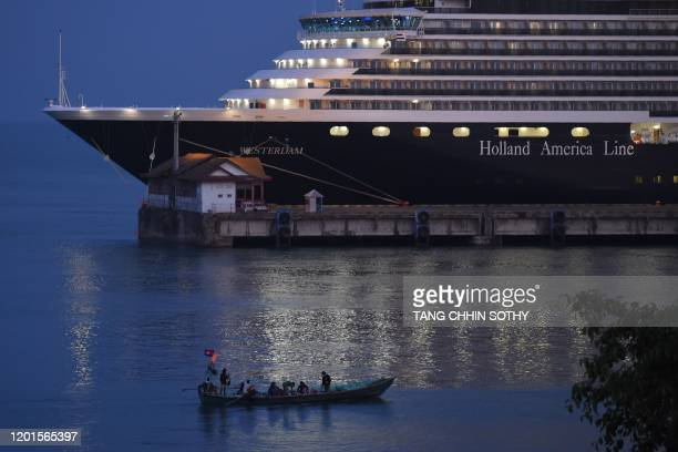 A fishing boat passes by the Westerdam cruise ship in Sihanoukville on February 18 where the liner on February 13 docked after being refused entry at...