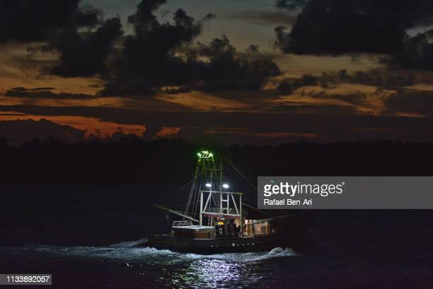 fishing boat sailing at dusk light into the ocean - rafael ben ari stock pictures, royalty-free photos & images