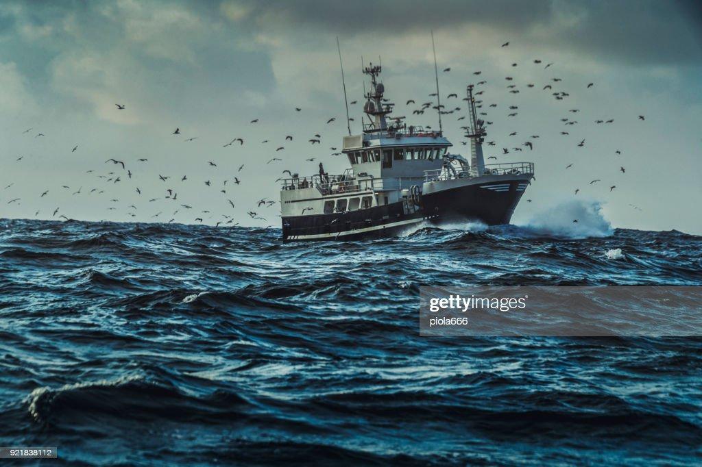 Fishing boat sailing at rough sea : Stock Photo