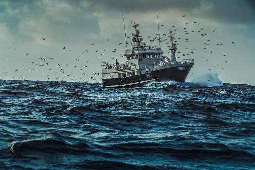 Fishing boat sailing at rough sea 921838112