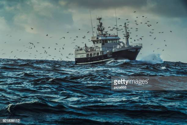 fishing boat sailing at rough sea - boat stock pictures, royalty-free photos & images