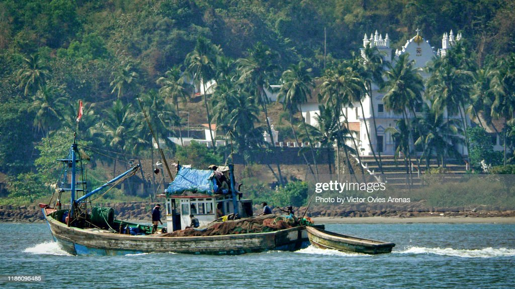 Fishing boat sailing in the Mandovi river with palm trees and colonial Portuguese church in the background in Panaji, Goa, India : Foto de stock