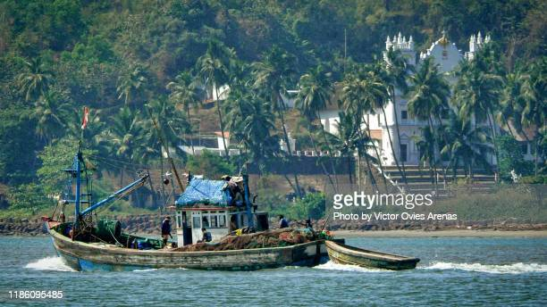 fishing boat sailing in the mandovi river with palm trees and colonial portuguese church in the background in panaji, goa, india - victor ovies fotografías e imágenes de stock