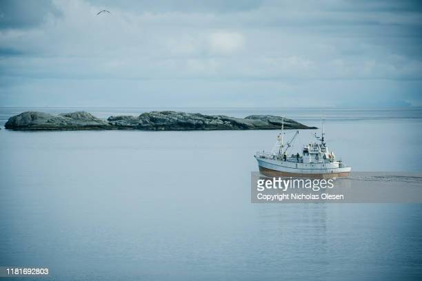 fishing boat sailing past norwegian island - fishing boat stock pictures, royalty-free photos & images